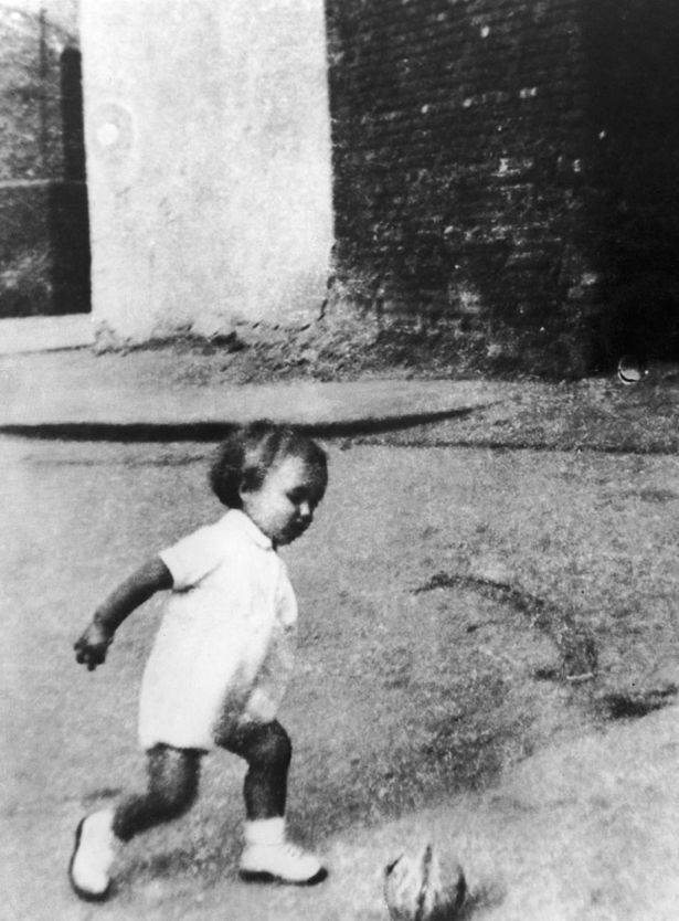 So young- George Best plays football in the street in this rare family photo, taken around 1948